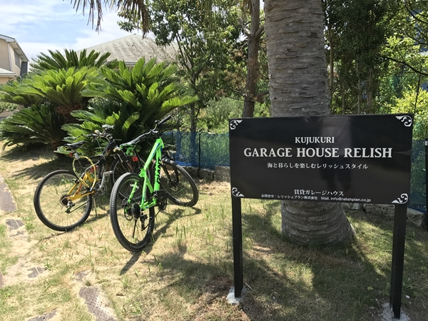 ガレージハウスのシンボルツリーのココヤシの木と看板